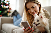 Young woman making selfie with her dog at home