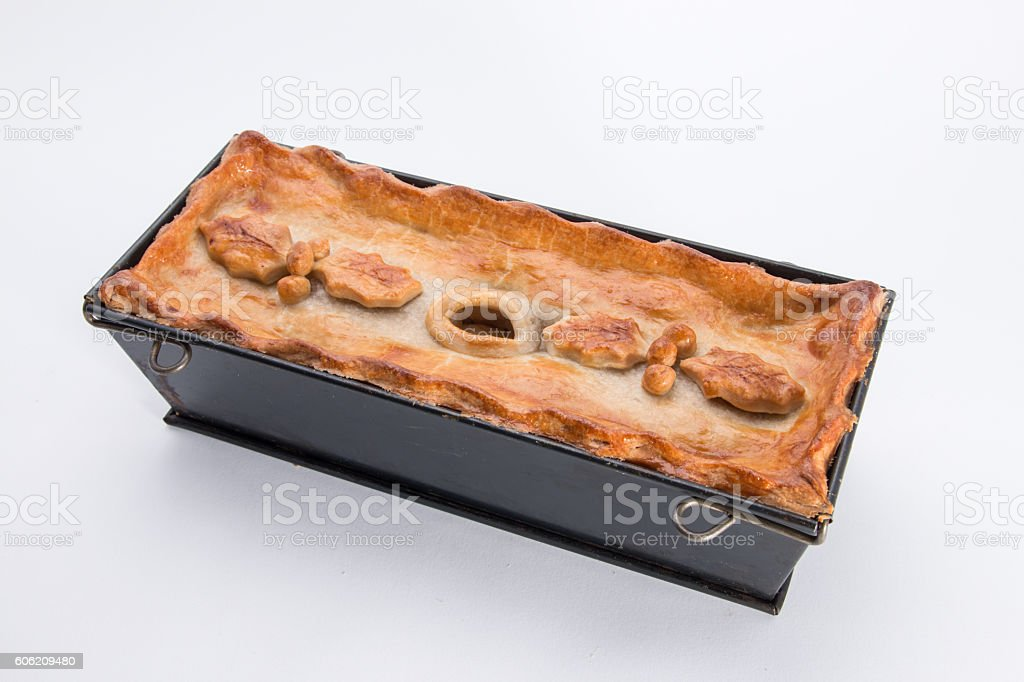 Christmas pie,   baking tin with holly leaf and berry decoration stock photo