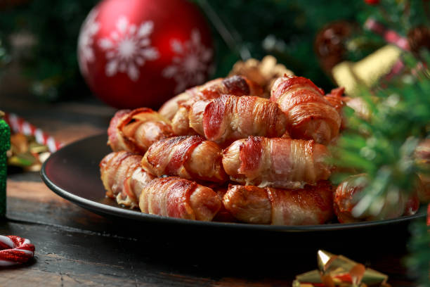 Christmas Pigs in blankets, sausages wrapped in bacon with decoration, gifts, green tree branch on wooden rustic table stock photo
