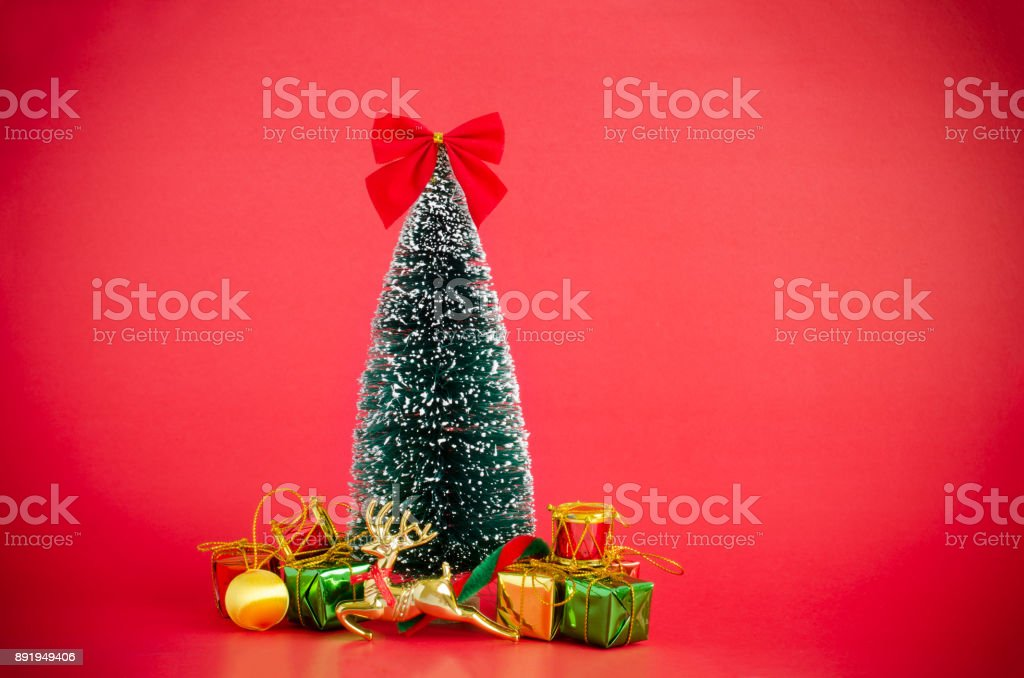 Christmas pine tree cover with snow decorating with Xmas ornaments; red, green and gold wrapped gift boxes, golden reindeer, red ribbon and candy cane over red background with copy space for holidays stock photo