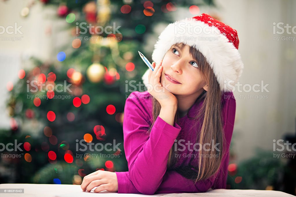 Christmas portrait of a little girl writing letter to santa stock photo