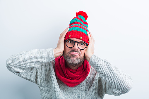 Christmas Portrait Of Angry Nerdy Man Wearing Elf Cap Stock Photo - Download Image Now
