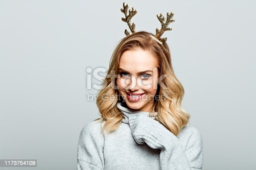 Mid adult beautiful woman wearing sweater and reindeer horns standing against grey background and smiling at camera.