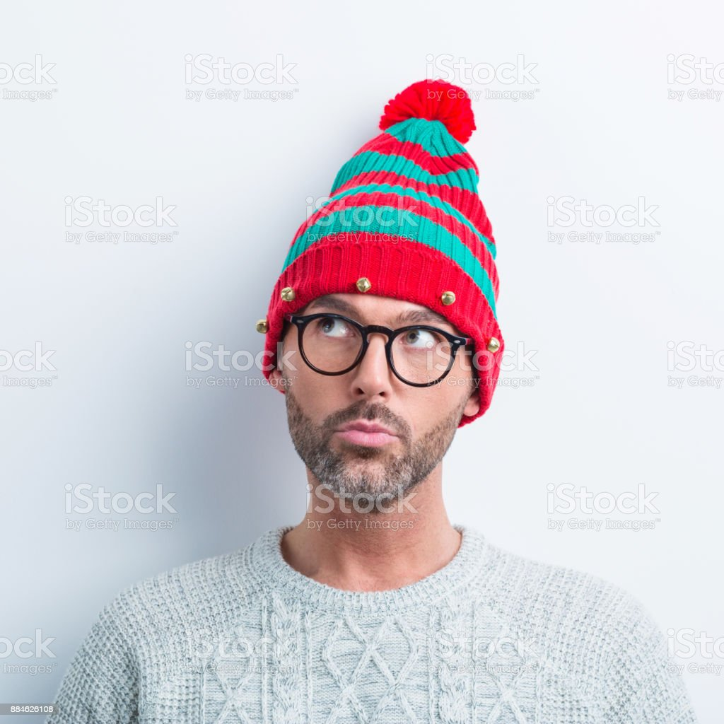 Christmas portrait of curious nerdy man wearing elf cap Funny christmas portrait of nerdy man wearing elf cap, looking away. Man wearing winter sweater standing against white background. 35-39 Years Stock Photo
