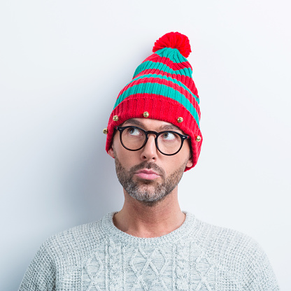 Christmas Portrait Of Curious Nerdy Man Wearing Elf Cap Stock Photo - Download Image Now