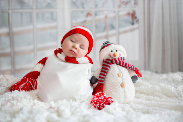 christmas portrait of cute little newborn baby boy, wearing santa hat - christmas families stock photos and pictures