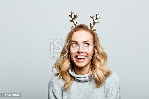Mid adult beautiful woman wearing sweater and reindeer horns standing against grey background, looking up and laughing.