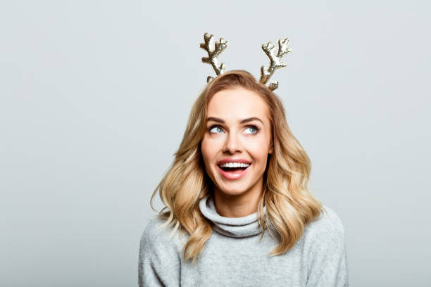 Christmas portrait of excited beautiful woman, close up of face stock photo Mid adult beautiful woman wearing sweater and reindeer horns standing against grey background, looking up and laughing. excited stock pictures, royalty-free photos & images
