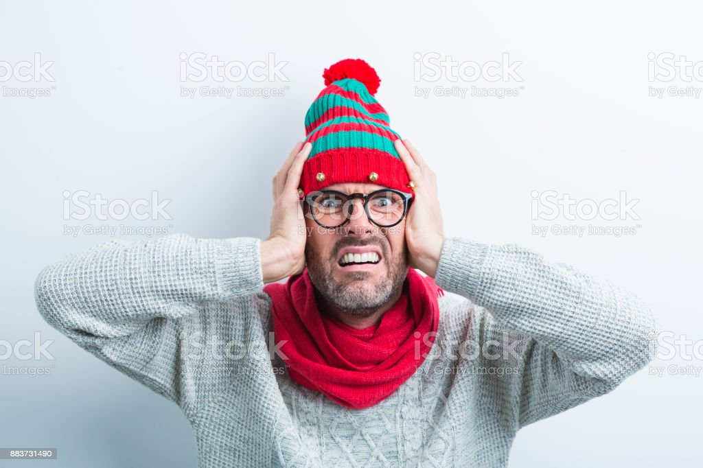 Christmas portrait of fearful nerdy man wearing elf cap Christmas portrait of fearful nerdy man wearing elf cap and red scarf. Man wearing winter sweater covering his ears against white background. Adult Stock Photo