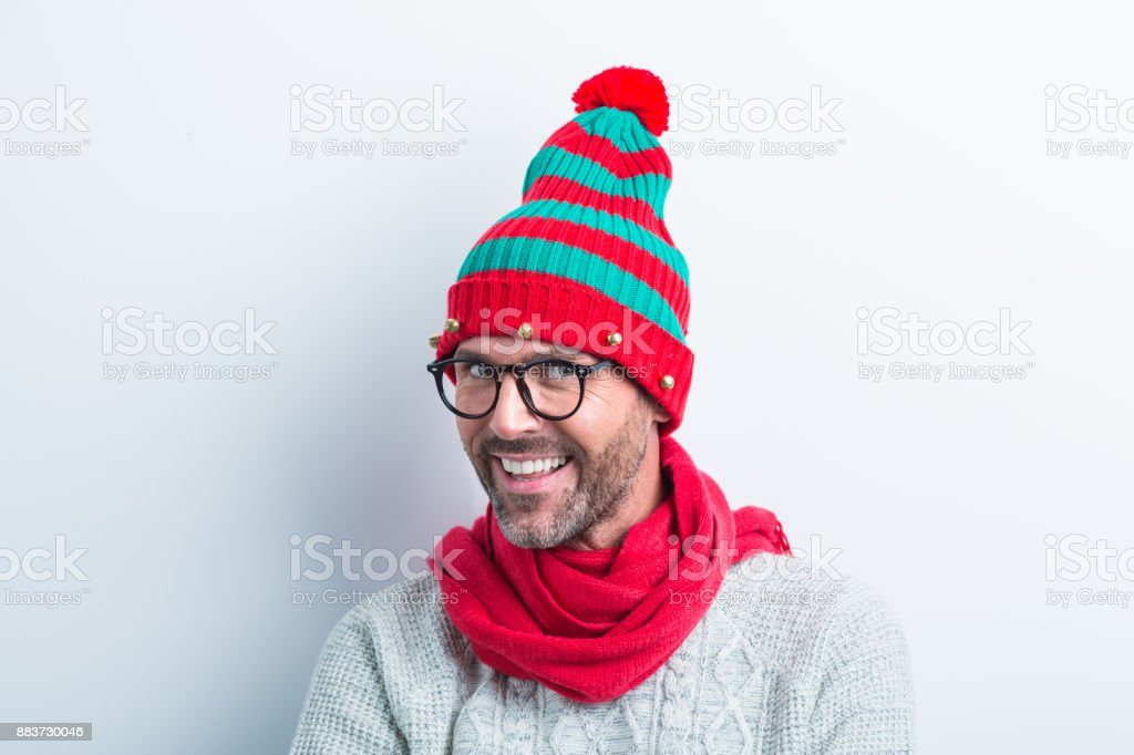 Christmas portrait of happy nerdy man wearing elf cap Funny christmas portrait of nerdy man wearing elf cap and red scarf. Happy man wearing winter sweater against white background. 35-39 Years Stock Photo