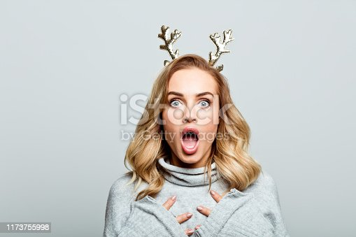 Mid adult beautiful woman wearing sweater and reindeer horns standing against grey background, shouting at the camera.