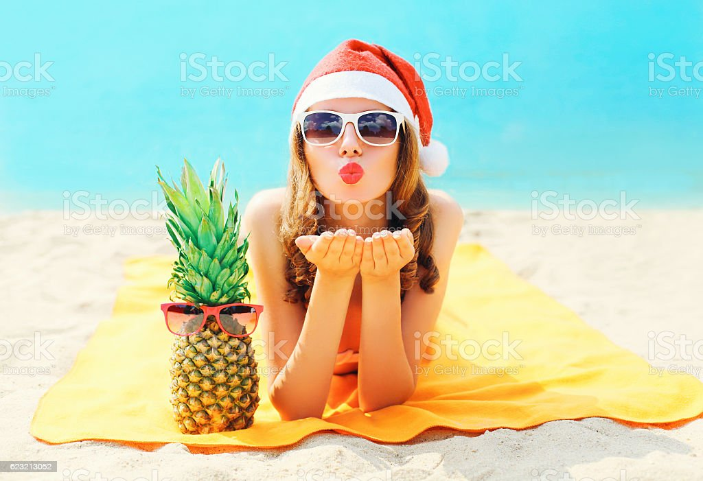 Christmas portrait woman in santa hat sends air kiss stock photo