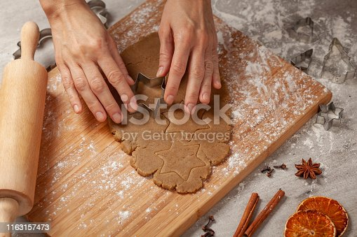 Preparing homemade gingerbreads on a wooden board, next to it there are forms for punching gingerbreads, kitchen roll, baking sheet