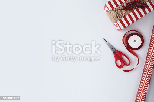 flat lay with christmas present, wrapping paper, ribbon and scissors isolated on white tabletop