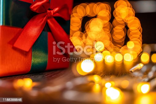 507751629 istock photo Christmas present - close-up, defocused Christmas lights in background, bokeh 1188388846