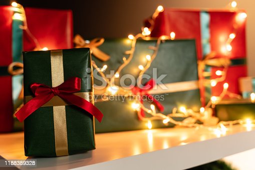507751629 istock photo Christmas present in front, Christmas lights  and presents in background, bokeh 1188389328