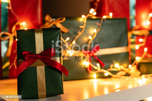 507751629 istock photo Christmas present in front Christmas lights  and presents in background 1187813163