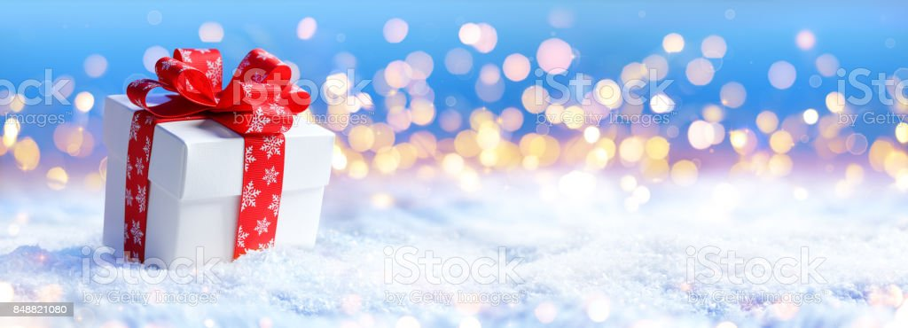 Christmas Present On Snow With Light Defocused stock photo