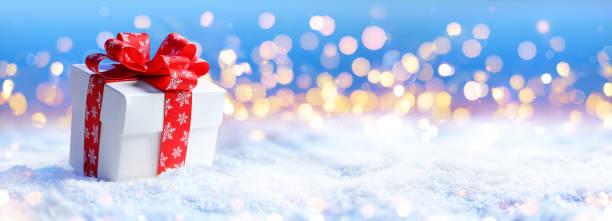 Christmas Present On Snow With Light Defocused stock photo