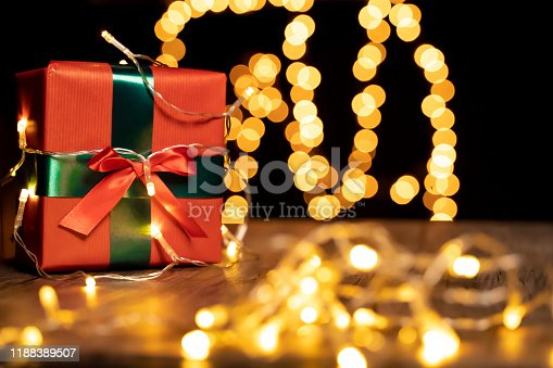 507751629 istock photo Christmas present on wooden table, defocused Christmas lights in background, bokeh 1188389507