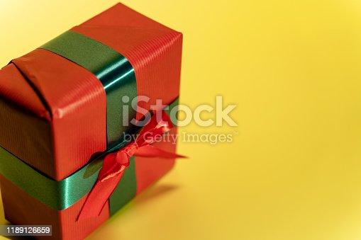 507751629 istock photo Christmas present on yellow background 1189126659