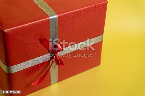 507751629 istock photo Christmas present on yellow background 1189126740