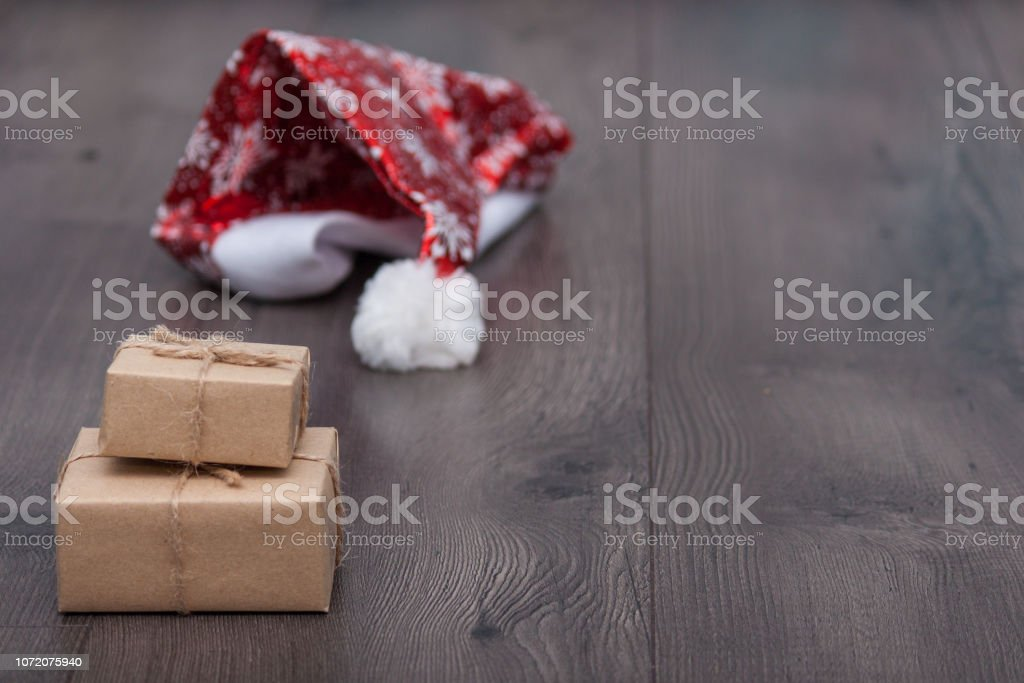 Christmas present or box from Secret Santa with Santa hat on wooden...