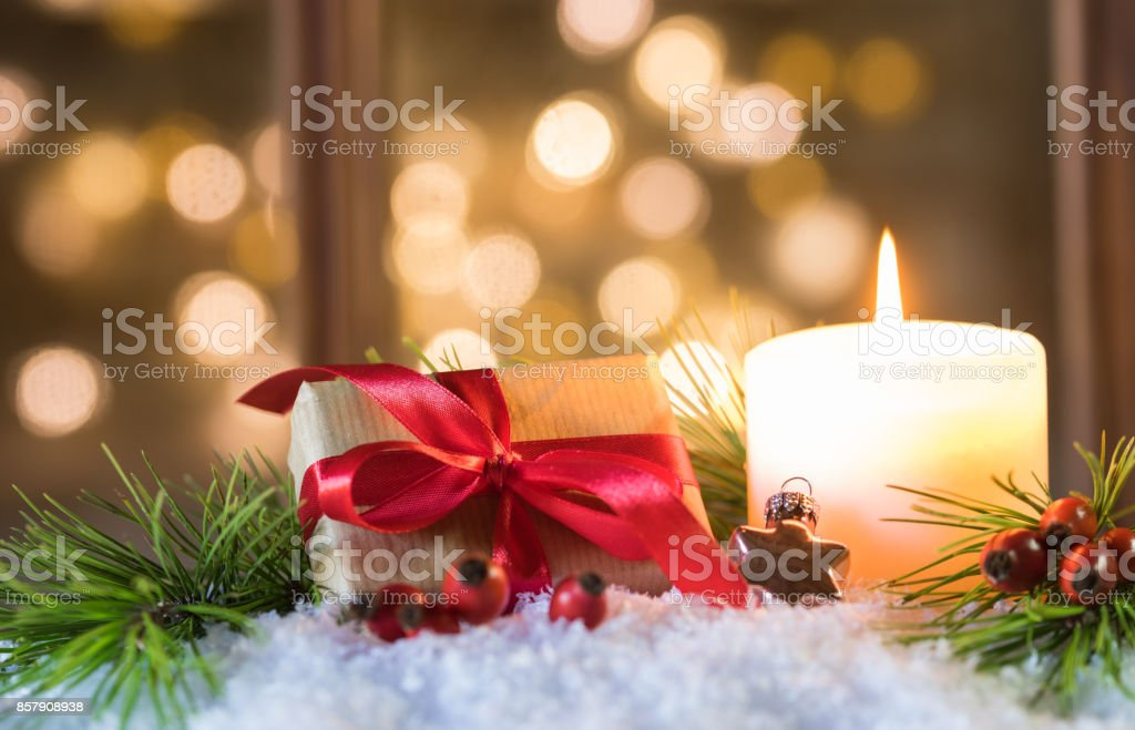 Christmas present with candlelight and glittering lights background stock photo