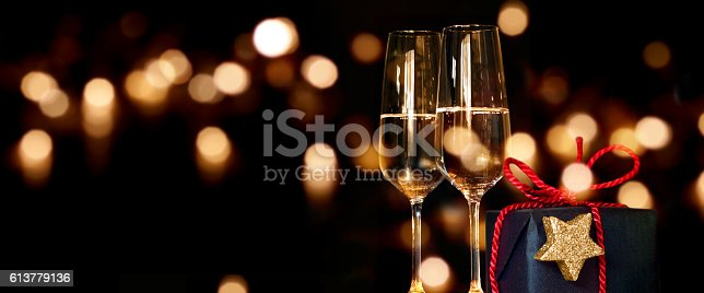 istock Christmas present with champagne glasses 613779136