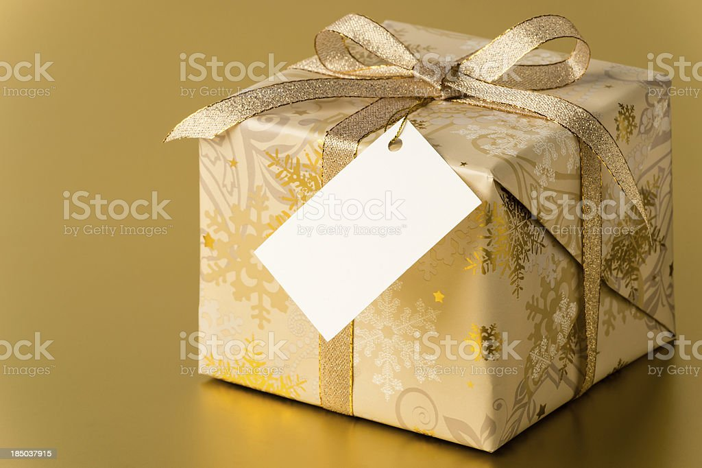 Christmas present with gold ribbon and blank tag, copy space stock photo