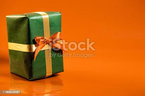 507751629 istock photo Christmas present with orange ribbon on orange background 1189949497