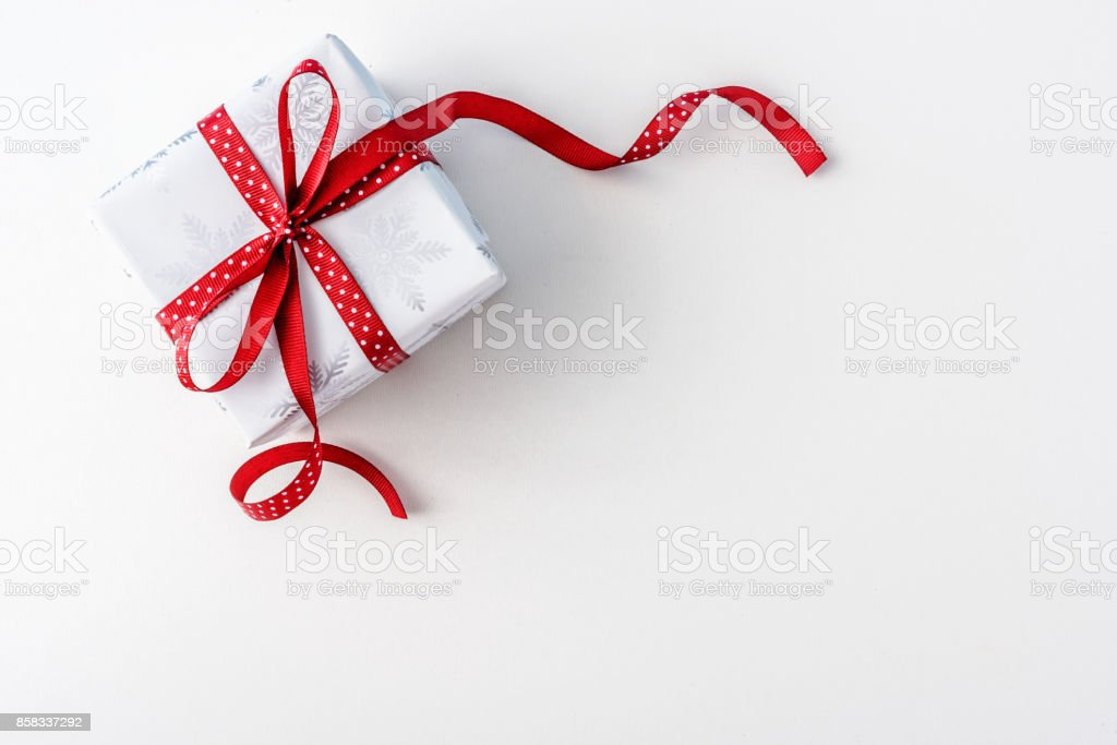 Christmas present with red dotted ribbon - holiday background stock photo
