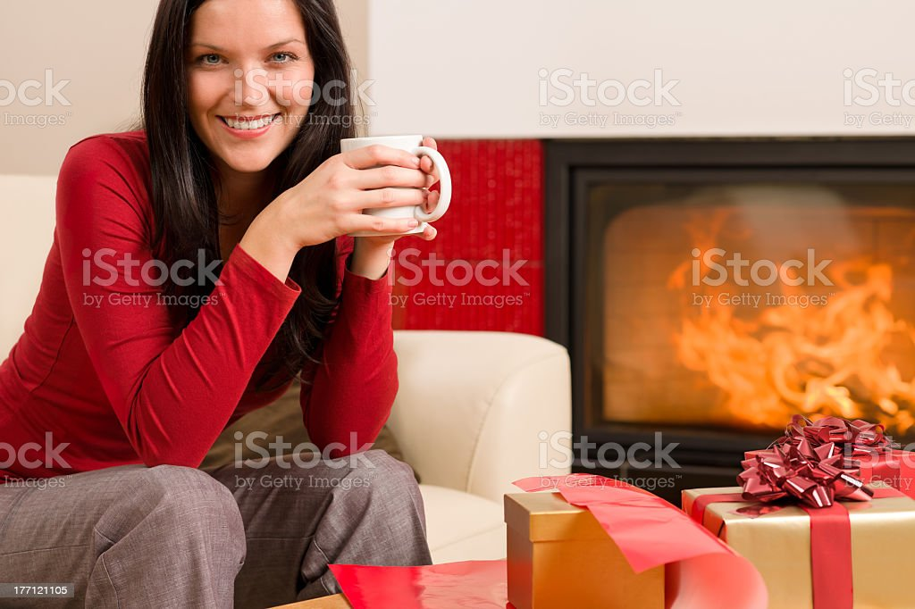 Christmas present wrap woman drink home fireplace royalty-free stock photo