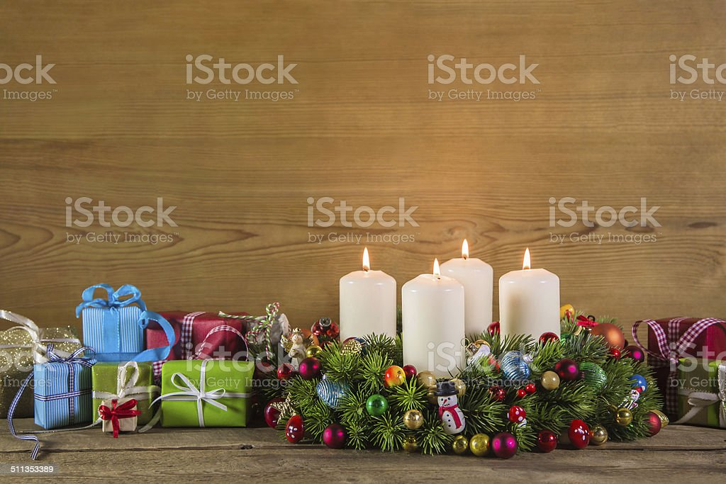 Christmas presents and advent wreath on wooden colorful background...