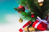 Christmas presents and decorated tree against ocean background
