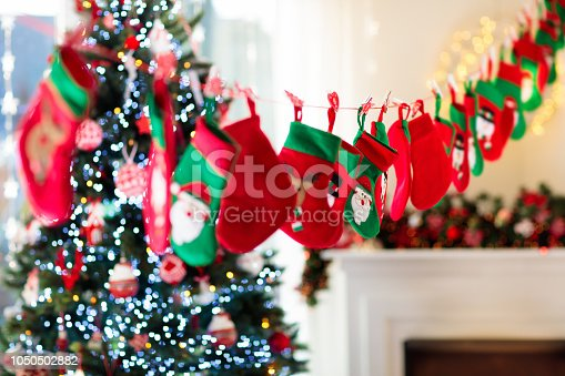 Christmas presents in green and red socks. Candy and gifts in kids advent calendar on winter morning. Decorated Christmas tree for family with children. Seasonal holiday decoration.