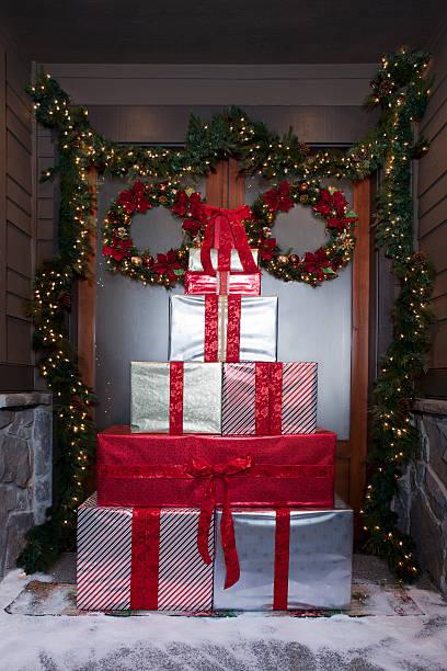weihnachten geschenke vor schnee tür mit kranz und blumenkranz - deko hauseingang weihnachten stock-fotos und bilder