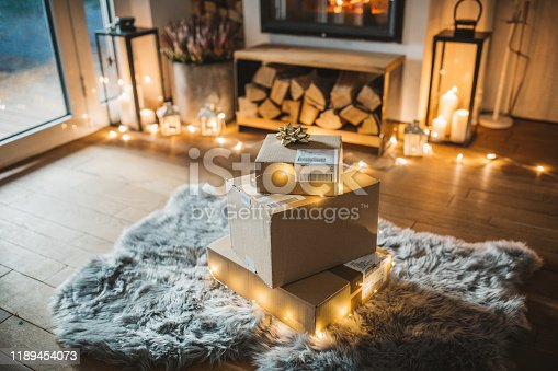 Cozy living room winter interior with fireplace, presents ordered online and delivered wait in front of fireplace.