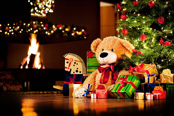 Christmas presents Christmas gifts under christmas tree with fireplace in background. christmas teddy bear stock pictures, royalty-free photos & images