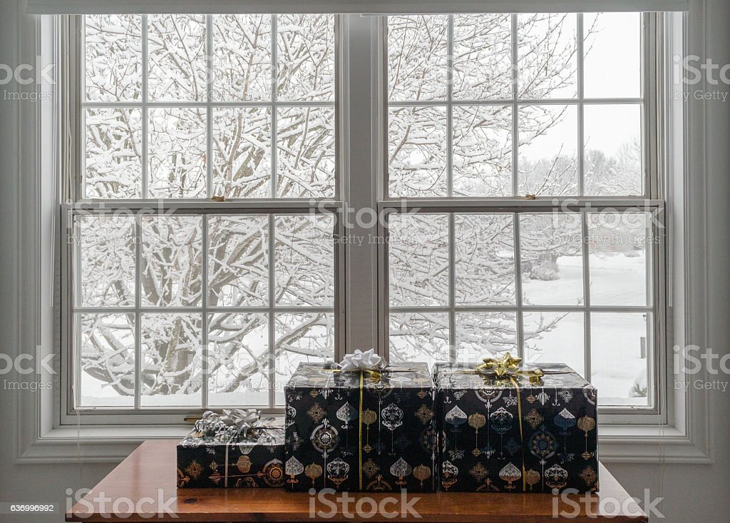 Christmas Presents Under A White Window Looking Outside Stock Photo
