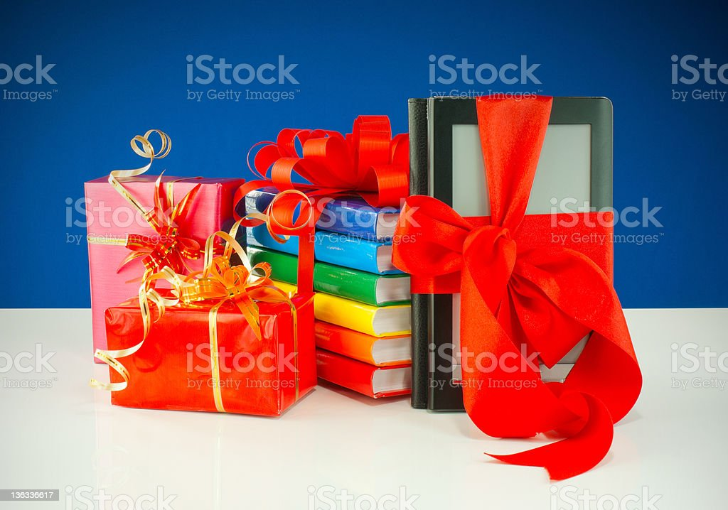 Christmas presents with electronic book reader against blue background stock photo