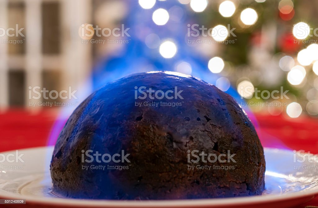 Christmas Pudding on a table, with a Christmas tree in the background stock photo
