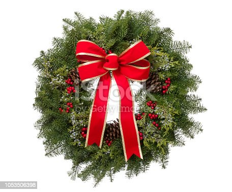 Christmas real pine wreath arrangement with a big red bow isolated on white