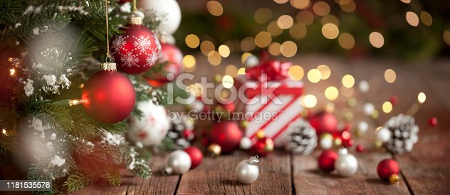Christmas red and white baubles with a candy cane striped gift box on an old wood background