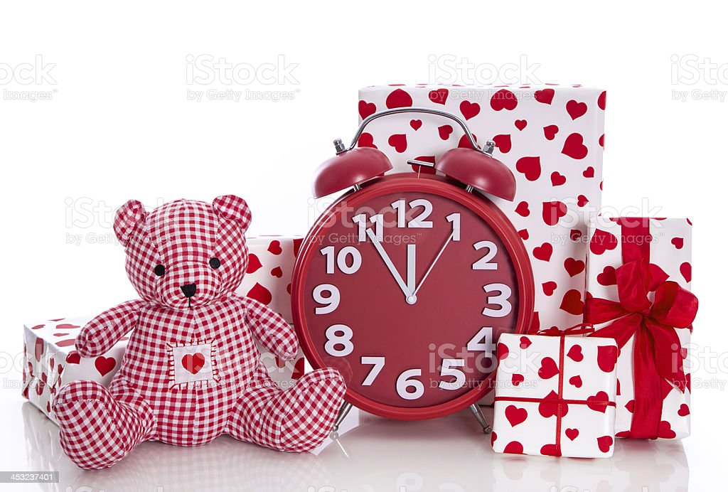 Christmas: red and white presents with clock plus teddy bear. stock photo