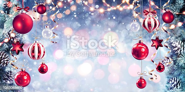 istock Christmas - Red Baubles Hanging With Fir Branches In Shiny Background 1063088800