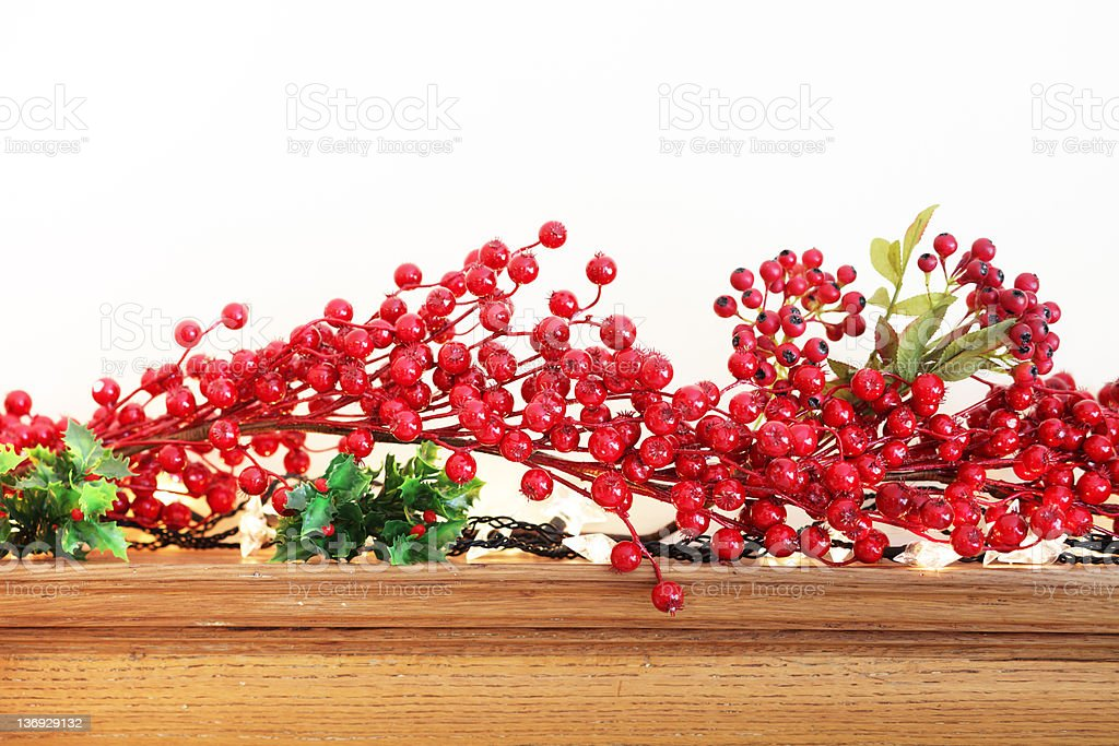 Christmas Red Berry Garland on Wooden Fireplace royalty-free stock photo