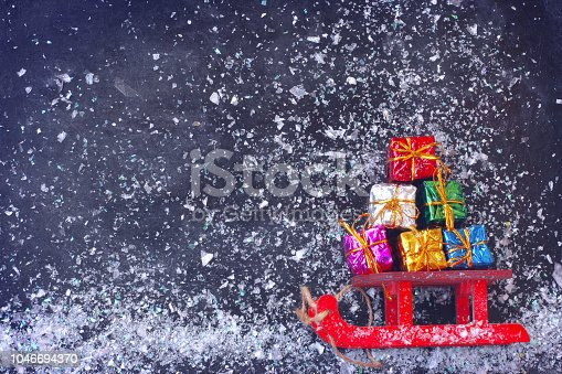 istock Christmas red sled carry bunch of colorful gift box 1046694370
