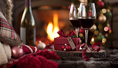 Christmas Red Wine in Front of the Cozy Fireplace and Christmas Tree with Gifts