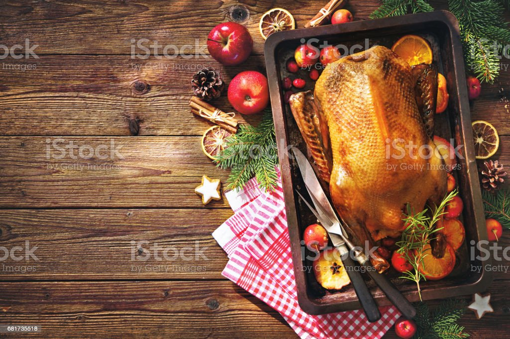 Christmas roast duck with apples and oranges on baking tray stock photo
